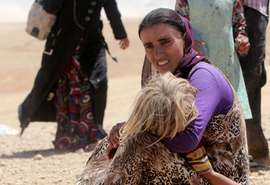 A displaced woman and child from minority Yazidi sect, fleeing violence from forces loyal to Islamic State in Sinjar town, ride truck and donkey as they make way towards Syrian border, on outskirts of Sinjar mountain