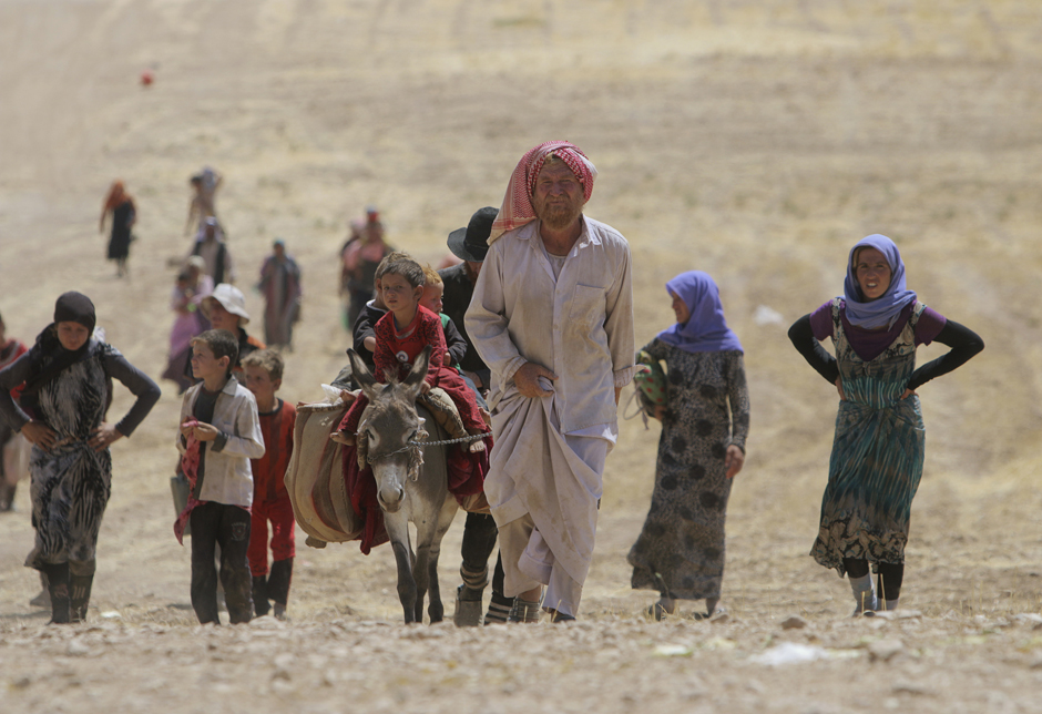 Displaced people from minority Yazidi sect, fleeing violence from forces loyal to Islamic State in Sinjar town, walk as they make way towards Syrian border
