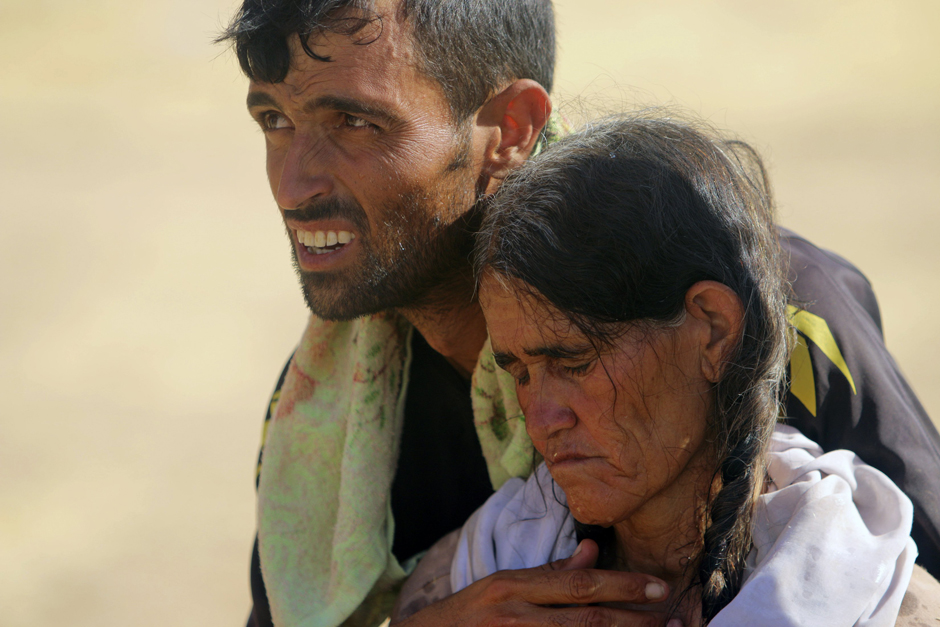 A displaced man and a woman from the minority Yazidi sect, fleeing violence from forces loyal to the Islamic State in Sinjar town, walk towards the Syrian border, on the outskirts of Sinjar mountain, near the Syrian border town of Elierbeh of Al-Hasakah G