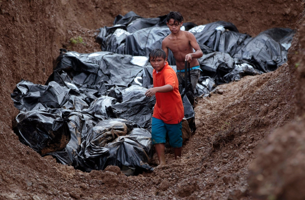 Image: Two boys help to fill a large grave with body bags at the Basper public cemetery in the  typhoon-hit city of Tacloban