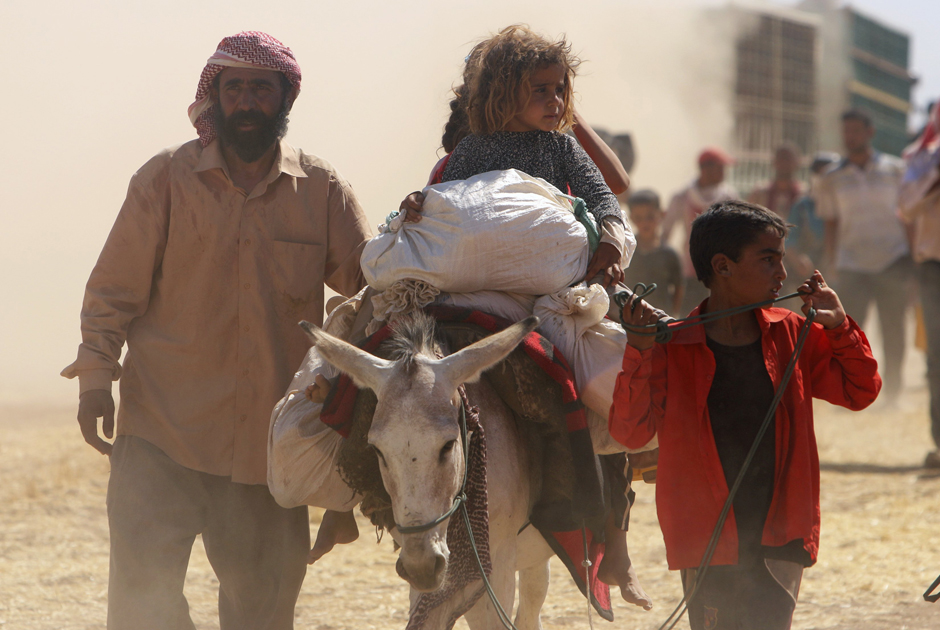 Displaced people from the minority Yazidi sect, fleeing violence from forces loyal to the Islamic State in Sinjar town, walk towards the Syrian border as others ride on a donkey on the outskirts of Sinjar mountain, near the Syrian border town of Elierbeh