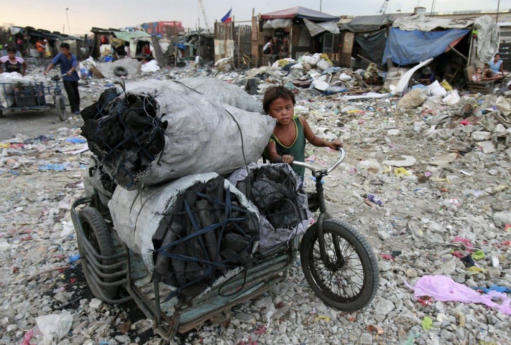 this-boy-pushes-a-cart-full-of-charcoal-which-was-made-at-a-garbage-dump-in-tondo-philippines
