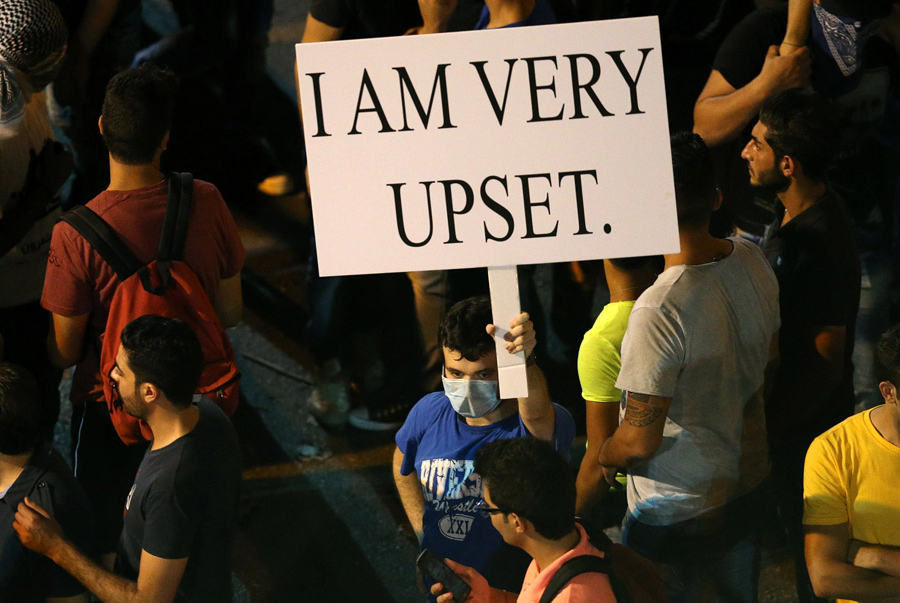 FILE - In this Saturday, Aug. 29, 2015 file photo, a Lebanese anti-government protester holds a placard during a demonstration against the on-going trash crisis and alleged government corruption, in Beirut, Lebanon. (AP Photo/Hussein Malla, File)