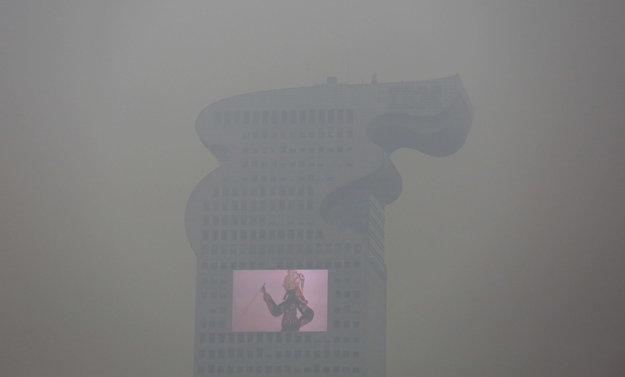 "A building and a large screen are seen through thick smog in Beijing December 8, 2015 as China's capital issues its first ever ""red alert"" for pollution. REUTERS/Damir Sagolj - RTX1XOBB"