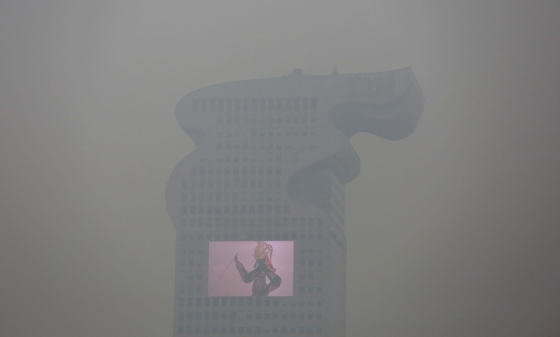 """A building and a large screen are seen through thick smog in Beijing December 8, 2015 as China's capital issues its first ever """"red alert"""" for pollution. REUTERS/Damir Sagolj - RTX1XOBB"""