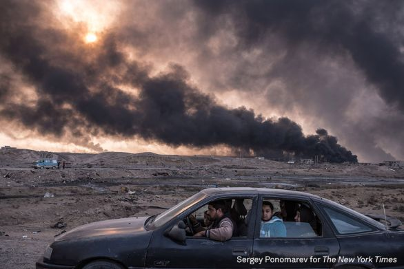 A family flees the fighting in Mosul, Iraq's second-largest city, as oil fields burned in Qayyara, Iraq, on November 12, 2016. In its sixth week, the military campaign to retake Mosul from the Islamic State had bogged down in a grueling fight. Seeking to escape the bloodshed, more civilians than ever took the risk of evacuation, hoping to find help if they could make it past the militants' gun range. By mid-December 2016, up to one million people were trapped inside the city, running low on food and drinking water and facing the worsening cruelty of Islamic State fighters.